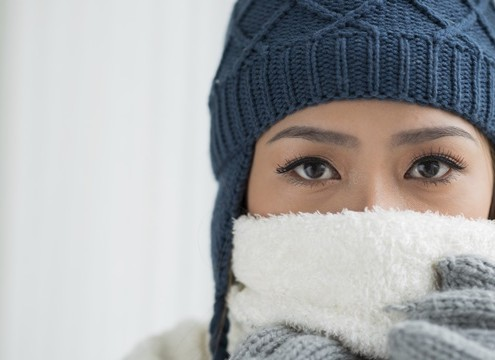 Copy-spaced portrait of a young frozen woman in winter wearing